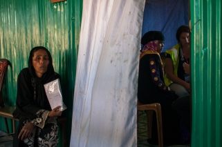 A woman waits for her turn to go behind the curtain and see the doctor at the field clinic near Balukhali Refugee Camp. Photo by Mike Kai