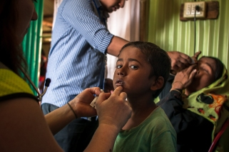 A child has a lip sore inspected by a doctor while a translator helps his mother put in eye drops to treat her complaint of blurry vision. Photo by Mike Kai